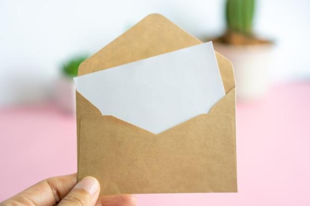 Tarjeta con sobre, tiene espacio para texto. sobre marrón con un trozo de papel blanco en blanco.