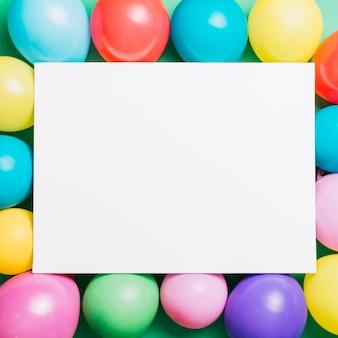Tarjeta de tablón blanco sobre los globos de colores.