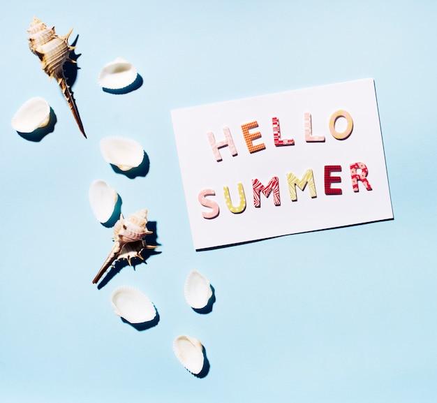 Tarjeta con texto hola verano y conchas marinas.