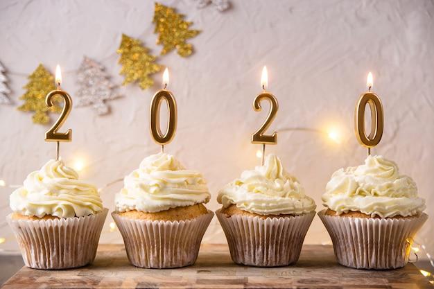 Tarjeta de vacaciones de año nuevo 2020 con luces y velas
