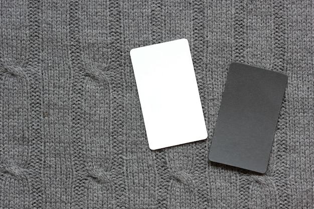 Tarjeta vacía en blanco y negro sobre un fondo gris tejido, vista superior. maqueta, creador de escenas.