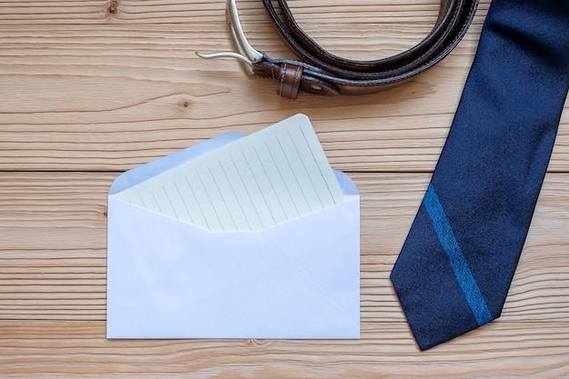 Tarjeta vacía con corbata azul y cinturón sobre fondo de madera con espacio de copia