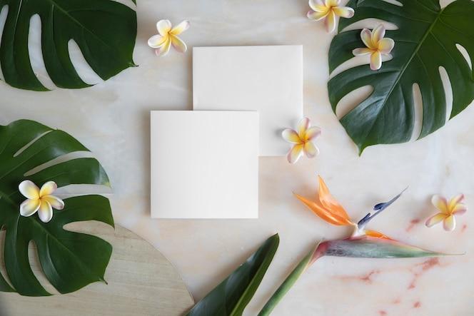 Tarjeta vacía con sobre en mesa de mármol y flores tropicales.