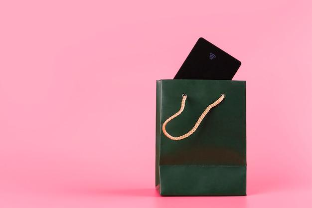 Tarjeta de viaje dentro de la bolsa verde sobre fondo rosa.