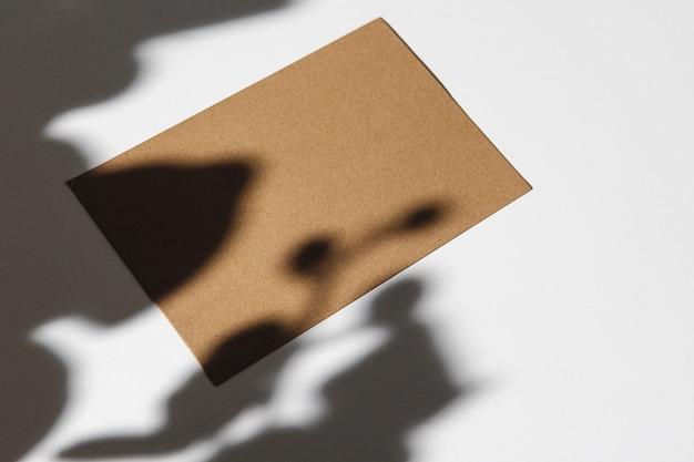 Tarjeta de visita beige sobre fondo blanco con sombra de follaje