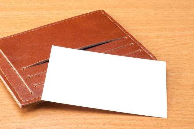 Tarjeta de visita blanca en blanco con portatarjetas de cuero marrón en mesa de madera