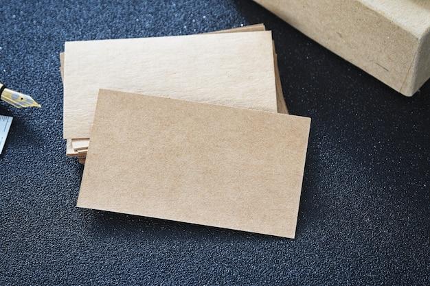 Tarjeta de visita en blanco se burlan de cartón en la mesa para el diseño de contacto de negocios