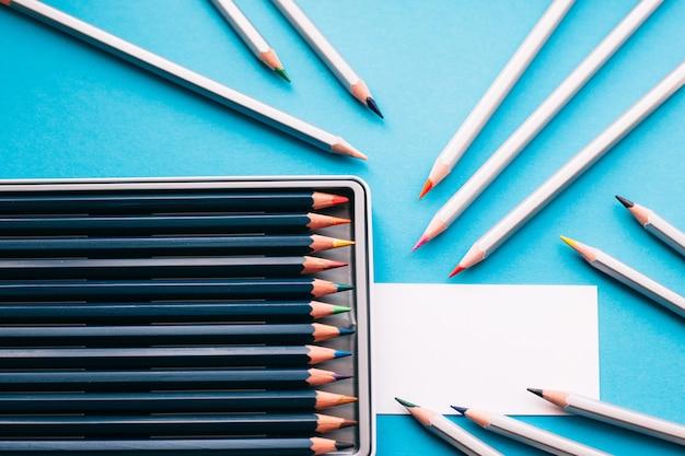 Tarjeta de visita en blanco con lápices de colores sobre el escritorio azul.