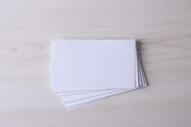 Tarjeta de visita en blanco sobre fondo de madera. papelería corporativa, maqueta de marca. escritorio de diseño creativo. endecha plana. copie el espacio para el texto. plantilla para identificación.