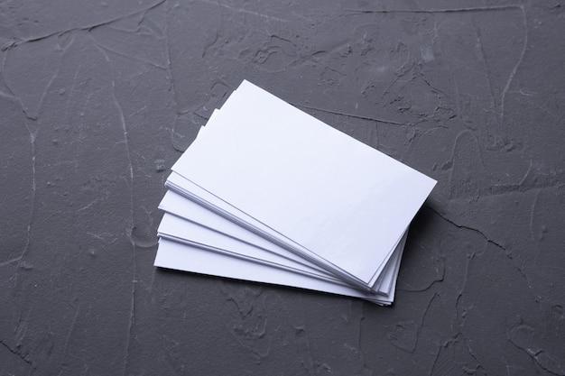 Tarjeta de visita en blanco sobre fondo de roca beton. papelería corporativa, maqueta de marca. escritorio de diseño creativo. endecha plana. copie el espacio para el texto. plantilla para identificación.
