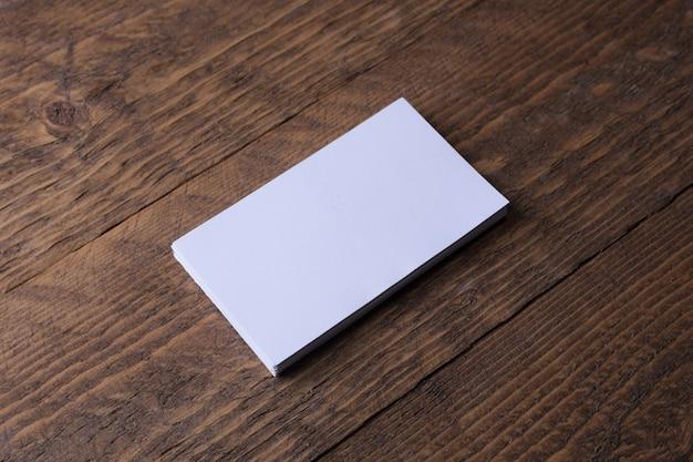 Tarjeta de visita en blanco sobre superficie de madera