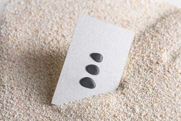 Tarjeta de visita mínima con piedras zen en concepto de bienestar