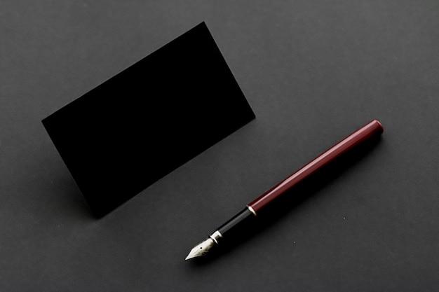 Tarjeta de visita negra en blanco para maqueta y bolígrafo vintage, marca de lujo y diseño de identidad corporativa