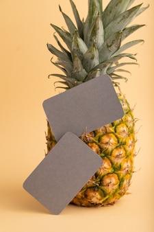 Tarjeta de visita de papel gris con piña madura sobre fondo naranja pastel. vista lateral, copie el espacio.