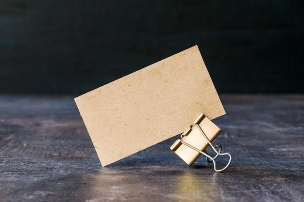 Tarjeta de visita de papel reciclado artesanal con clip de carpeta de metal en mesa