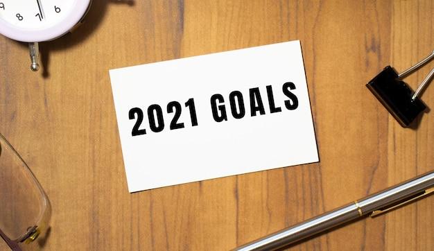 Una tarjeta de visita con el texto objetivos 2021 se encuentra en una mesa de oficina de madera