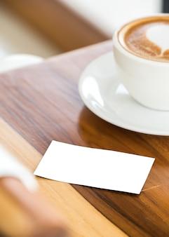 Tarjeta de visita vacía simulacro con café caliente en la mesa de madera
