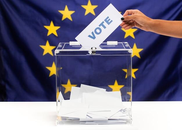 Tarjeta de votación sostenida a mano y puesta en la urna
