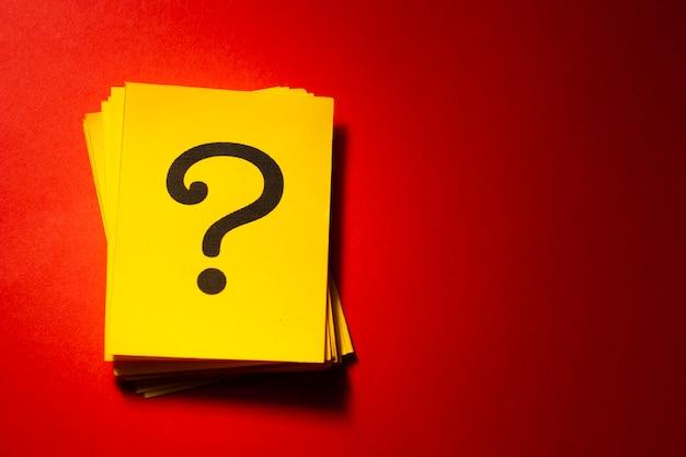 Tarjetas amarillas apiladas con signo de interrogación impreso