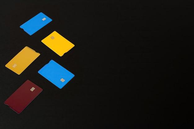 Tarjetas bancarias de diferentes colores sobre mesa negra. tarjetas para comprar el black friday