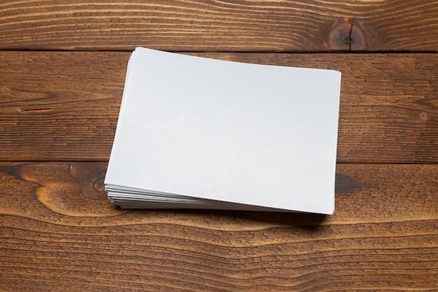Tarjetas blancas en blanco sobre fondo de madera.