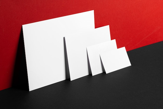 Tarjetas blancas en blanco sobre fondo de papel rojo y negro, espacio de copia