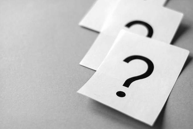 Tarjetas blancas con signos de interrogación impresos