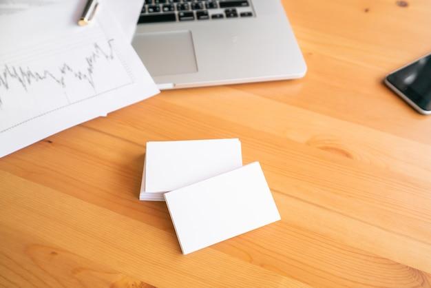 Tarjetas en blanco y laptop en superficie de madera
