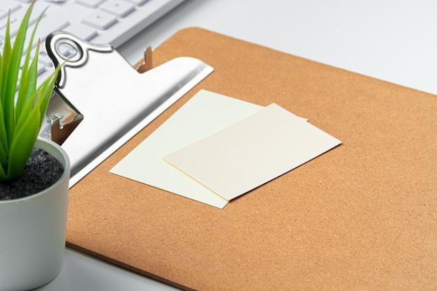 Tarjetas en blanco con suministros y teclado en la mesa de oficina.