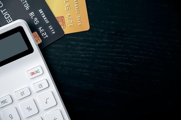 Tarjetas de crédito y calculadora en mesa de madera negra