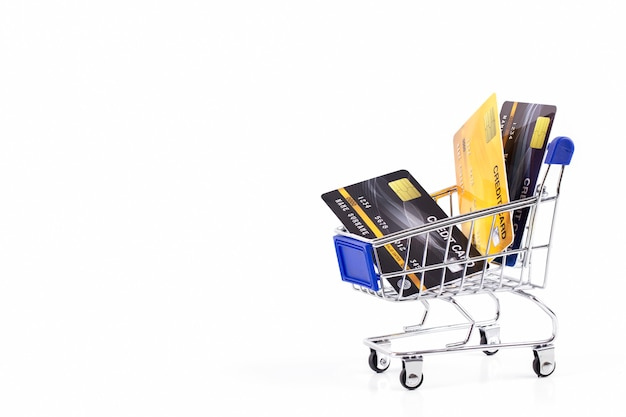 Tarjetas de crédito en un carrito de compras aislado sobre fondo blanco