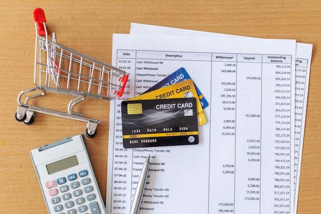 Tarjetas de crédito y carrito de supermercado y calculadora en extracto bancario en una mesa de madera