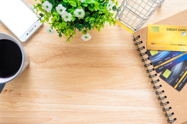 Tarjetas de crédito, cuaderno, árbol de maceta, teléfono inteligente, carrito de compras y taza de café sobre fondo de madera, banca en línea mesa de oficina de vista superior.