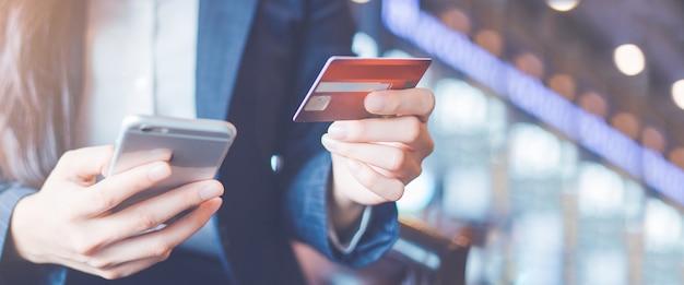 Tarjetas de crédito y smartphones del uso de la mano de la mujer de negocios. bandera de la tela.