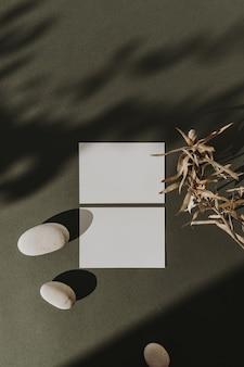 Tarjetas de hoja de papel en blanco con rama de flor seca, piedras y sombras de luz solar en verde oscuro
