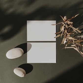 Tarjetas de hojas de papel en blanco con espacio de copia, rama de flor seca, piedras y sombras de luz solar en verde profundo