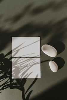 Tarjetas de hojas de papel en blanco, rama de flor seca, piedras y sombras de luz solar en verde oscuro