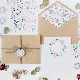 Tarjetas de invitación de boda, sobres artesanales, rosas rosadas y rojas y hojas verdes sobre blanco