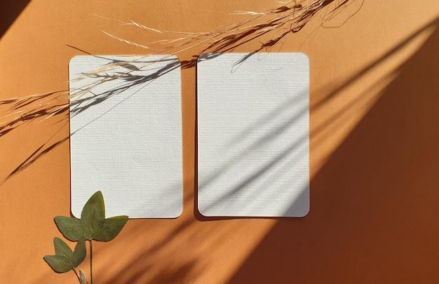 Tarjetas de invitación de felicitación de boda en blanco maquetas con hojas secas de plantas y hierbas sobre fondo de mesa de terracota con textura. elegante plantilla moderna para la identidad de marca. vista plana, vista superior