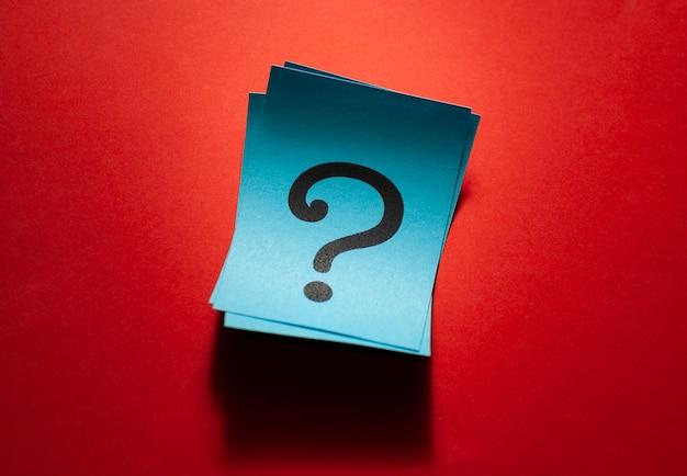 Tarjetas de papel azul rizadas con signos de interrogación