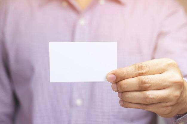 Las tarjetas de visita del asimiento de la mano del hombre de la gente muestran el frente de la exhibición de la tarjeta blanca en blanco o de la tarjeta de nombre de crédito del cartón. concepto de marca empresarial.