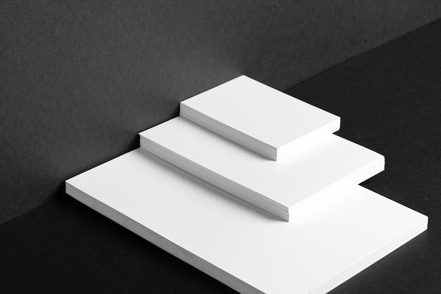 Tarjetas de visita blancas apiladas para la identidad de marca en la mesa negra