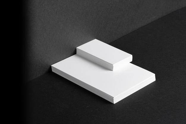 Tarjetas de visita blancas apiladas para identidad de marca sobre fondo negro, espacio de copia