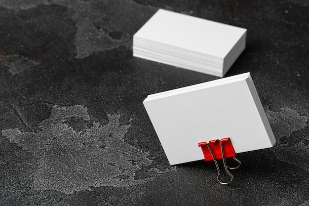 Tarjetas de visita blancas unidas con un clip sobre un fondo negro áspero