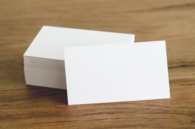 Tarjetas de visita en blanco en la mesa de madera.