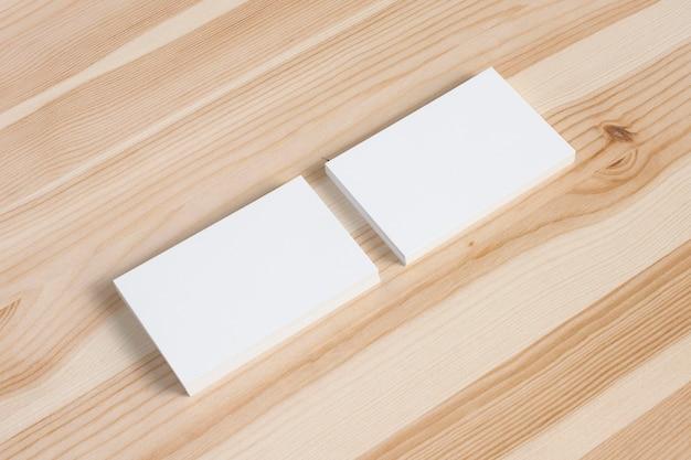 Tarjetas de visita en blanco stacs en el viejo escritorio de madera. plantilla para exhibir su presentación.