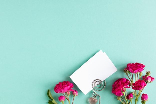 Tarjetas de visita de la maqueta en un fondo coloreado y una flor de la rosa, copyspace, topview.