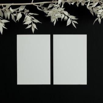Tarjetas de visita de papel en blanco con espacio de copia de maqueta sobre fondo negro con rama floral.