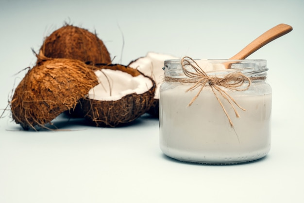 Tarro de aceite de coco cerca de partes de coco sobre un fondo coloreado
