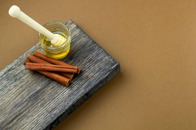 Tarro y canela de la miel de la visión superior en un espacio de la copia del fondo del marrón del tablero de madera